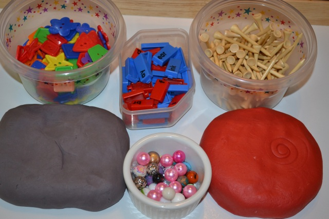We have some colored buttons, word links, golf tees, play dough, and a variety of beads and marbles.